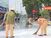 Tin tức - CSGT dầm mưa giúp người dân quét sơn bị đổ ra đường