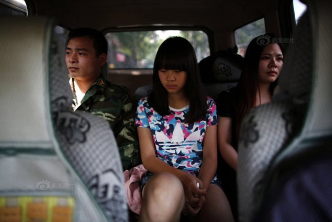 """Tình trạng trẻ em ngày càng chìm đắm vào thế giới ảo đã khiến nhiều bậc phụ huynh TQ quyết định tìm đến những trung tâm """"cai nghiện internet"""" để mong có giải pháp cứu con em mình khỏi """"căn bệnh"""" của xã hôi hiện đại này. Những trại cai nghiện internet ngày nay đã không còn là cái tên xa lạ ở Trung Quốc. Trong ảnh, một bé gái người Bắc Kinh đang đi kèm với giáo viên và giảng viên quân sự của mình vào """"trại""""."""