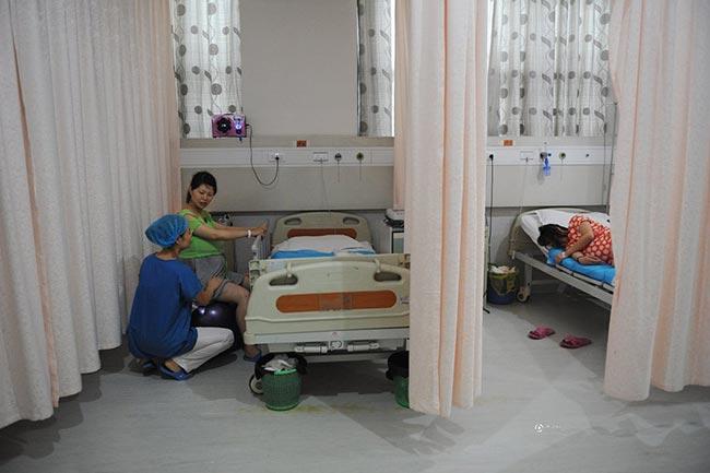 Phòng chờ sinh ở Trung Quốc cũng có khoảng 3-4 giường, được ngăn cách bởi cách tấm rèm kéo bằng vải mỏng.Trong phòngchờ sinh, thai phụ 9xGuo Jia đang bắt đầu được y tá hướng dẫn ngồi trên quả bóng sinh để luyện tập