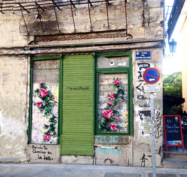 Bức tranh thêu hoa hồng đôi gắn bên trên bức tường cũ kỹ đã biến cánh cửa trở nên độc đáo và thu hút hơn.