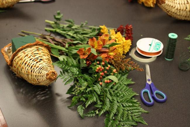 Nguyên vật liệu:  - 1 chiếc giỏ hình sừng dê  - 7 – 8 cành hoa lan màu cam, loại nhỏ  - 10 – 12 cành hoa cúc vàng và đỏ  - Lá cắm kèm: Dương xỉ, và lá cắt ra từ hoa  - Xốp cắm hoa (Ngâm trong nước 10 – 15 phút để xốp ngậm nước)  - Ruy băng lụa màu da cam  - Kéo, băng dính, dây théo mỏng  * Các bạn có thể tìm mua các loại giỏ tại các cửa hàng đồ mây tre đan trên chợ Hàng Khoai, chợ Đồng Xuân, hồ Thiền Quang… với giá từ 20 – 30 nghìn đồng/chiếc.  BÀI LIÊN QUAN:  Cắm hoa cúc để bàn đẹp trong 5 phút  Tặng chị em mẹo cắm hoa tươi lâu  Cắm hoa xen quả đơn giản, đẹp mắt  Cắm hoa hồng cho ngày cưới mê ly  4 mẫu cắm hoa với bí ngô độc đáo  Cắm cẩm tú cầu cho nhà đẹp hết cỡ  3 mẫu hoa đẹp cắm nhanh chỉ 3 phút  5 cách cắm hoa để bàn chị em mê tít