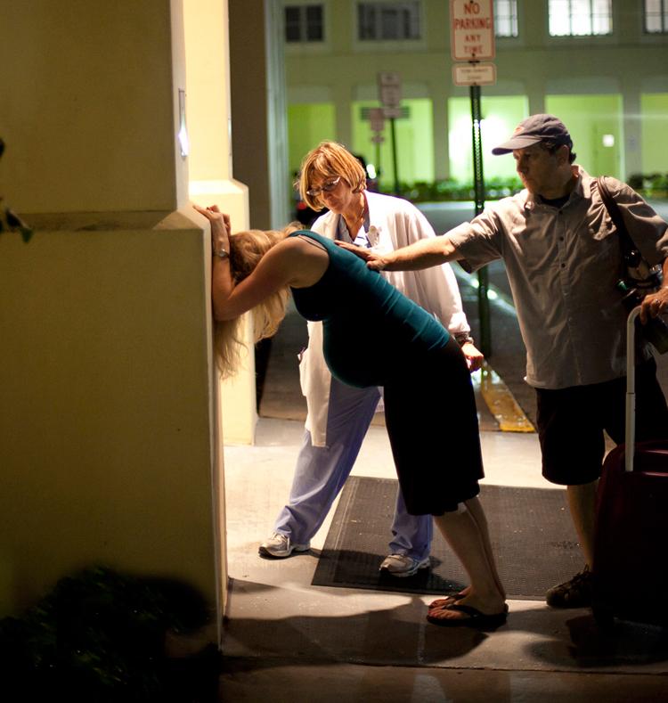 Trong lần mang thai thứ 2 này, chị Amy Beth (người Mỹ) đã nhờ nhiếp ảnh gia Emily Robinson chụp lại bộ ảnh sinh nở đẹp nhất. Thế nhưng chị không ngờ, bộ ảnh đón bé chào đời của chị lại 'khác người' đến thế.  Vì đây là lần sinh thứ 2 nên Amy Beth rất bình tĩnh. Khi nhận thấy những cơn đau chuyển dạ, chị đã ở nhà chờ cho đến khi cơn đau lên đến đỉnh điểm mới vào bệnh viện. Khi hai vợ chồng bắt xe vào bệnh viện, đồng thời chị cũng gọi điện cho nhiếp ảnh gia đến đó. Bác sĩ cũng đã sẵn sàng đón sản phụ Amy Beth nhưng tất cả mọi người đều không ngờ rằng chị sinh nhanh đến vậy.  Khi đến gần bệnh viện, chị Amy Beth đã bị vỡ ối và chỉ từ cổng bệnh viện vào đến phòng sinh, sau hai cơn rặn là em bé đã chào đời. Điều đặc biệt là bé chào đời ngay trên xe lăn khi sản phụ được di chuyển vào phòng sinh.  Trong ảnh, sản phụ Amy Beth và chồng vừa tới bệnh viện.