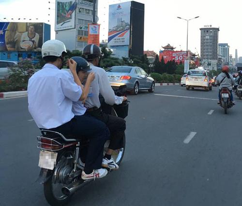 Hai học sinh vừa ngồi trên xe máy vừa tranh thủ ăn cơm hộp-2
