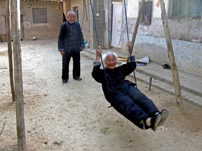 Một cặp vợ chồng già đang chơi đu quay trong sân giống như những đứa trẻ