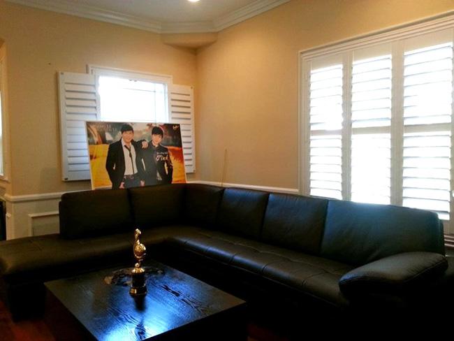 Bên trong phòng khách nổi bật hai gam màu trắng và vàng kem. Bộ sofa cùng chiếc bàn màu đen càng nổi bật, ấn tượng hơn. Quang Lê cũng đặt những tấm hình của mình và bạn bè đồng nghiệp ngay trong phòng khách.