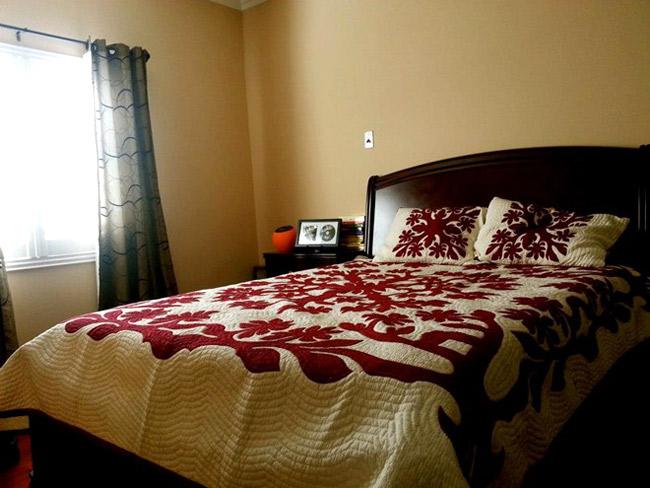 Phòng ngủ của Quang Lê không bày biện gì nhiều nên anh chọn bộ giường ngủ có họa tiết màu đỏ giúp căn phòng tươi tắn hơn.