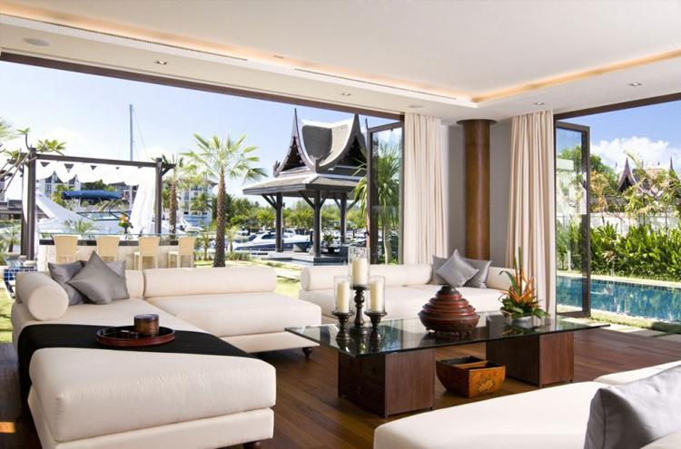 Nội thất trong nhà rất quý phái. Đây là phòng khách với tầm nhìn ra bể bơi, khu thư giãn và thấy lấp ló cả những du thuyền khủng đang đậu trước nhà. Bộ ghế sofa trắng làm không gian trở nên thanh lịch và dịu mắt.