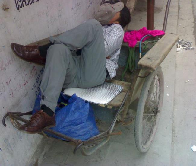 Anh đạp xích lô mệt nhoài sau một ngày làm việc, ngủ không cần biết đến ai