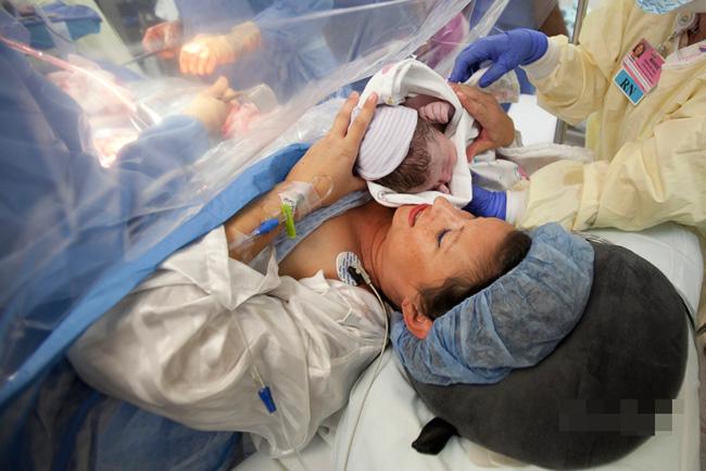 Và chỉ 20 phút sau bé đã được đưa về nằm trên bụng mẹ, mặc dù lúc này các bác sĩ vẫn tiếp tục khâu vết mổ cho cô.