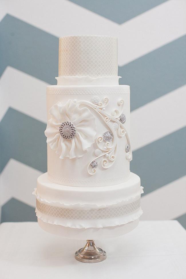 Những chiếc bánh cưới thường có màu trắng với ý nghĩa tượng trưng cho sự trong trắng, thuần khiết. Qua thời gian, chiếc bánh cưới dần nên không thể thiếu trong nhiều lễ cưới trên thế giới, kể cả ở Việt Nam. Vai trò của nó không còn dừng lại ở việc trang trí cho lễ cưới mà còn phần nào thể hiện cá tính của cô dâu chú rể,là biểu hiện của sự sang trọng, thanh lịch và sự no đủ, tràn trề, sự ngọt ngào của hạnh phúc vẹn tròn. Cùng nhau cắt bánh cưới cònlà một nghi lễ, một lời hứa hẹn mãi mãi sắt son, chung thủy, đồng hành bên nhau suốt cuộc đời.  Đây là hình ảnh một chiếc bánh cưới màu trắng rất thuần khiến và khá phổ biến trong nhiều lễ cưới.