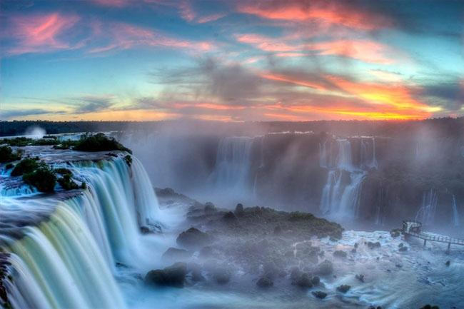 """Argentina vàBrazil  Nằm giữa biên giới Argentina và Brazil, Iguazu là thác nước gồm 275 bậc cấp trải rộng hơn 3km vách núi đá có rừng nhiệt đới bao phủ. Dòng thác lao xuống từ độ cao 82 mét với một thác lớn ấn tượng nhất có tên gọi """"Họng Quỷ"""", vốn là một hẻm núi cong hình chữ U chiếm gần phân nửa chiều ngang sông Iguazu."""