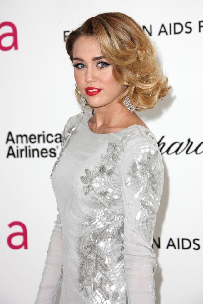Miley Cyrus đẹp quý phái như phụ nữ tuổi 35. Kiêu tóc gợn sóng lệch, kết hợp đầm ánh bạc in hoa khiến cô hoàn toàn mất đi vẻ trẻ trung.