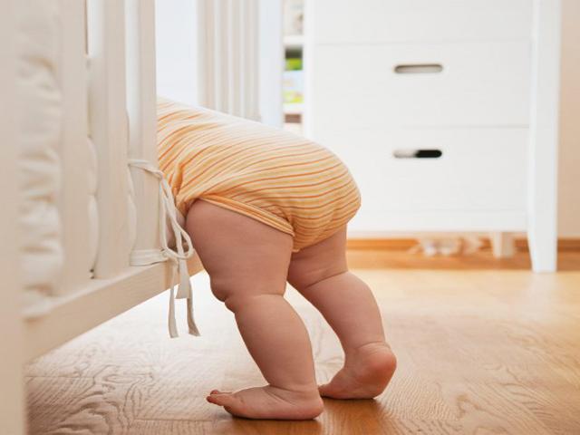 Đặt bé nằm sấp, khép hai chân và tìm dấu hiệu dị tật trật khớp háng nguy hiểm