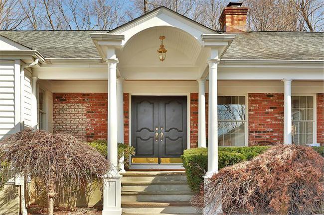 Lối vào căn nhà màu trắng với cánh cửa ra vào màu nâu sậm nổi bật.