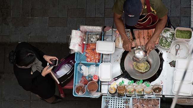 """1. Bangkok, Thái Lan  Ảnh street01Khu phố người Hoa (""""Yarowat"""") là một trong những quận nổi tiếng nhất về đồ ăn đường phố của Bangkok  Đã đến Bangkok thì không thể không ăn vặt trên đường, nơi các hàng quán vỉa hè ở đủ mọi khu vực khác nhau, bán đủ các món ngon ở đủ mọi khung giờ.  Dễ dàng bắt gặp những nhân viên vội vã ăn sáng với sữa đậu nành cùng tào phớ nước đường ở đầu phố, trong khi một nhóm khác gọi món xôi nước dừa cùng thịt gà xé thơm lừng cho bữa trưa ở cuối phố.  Những người theo phong cách cú đêm cũng được phục vụ tất tần tật mọi món từ mì phad Thái đến thịt gà satay nướng."""