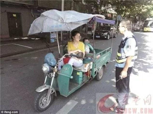 Bà mẹ gây tranh cãi khi vừa lái xe 3 bánh chở con phía sau, vừa cho bé khác  bú