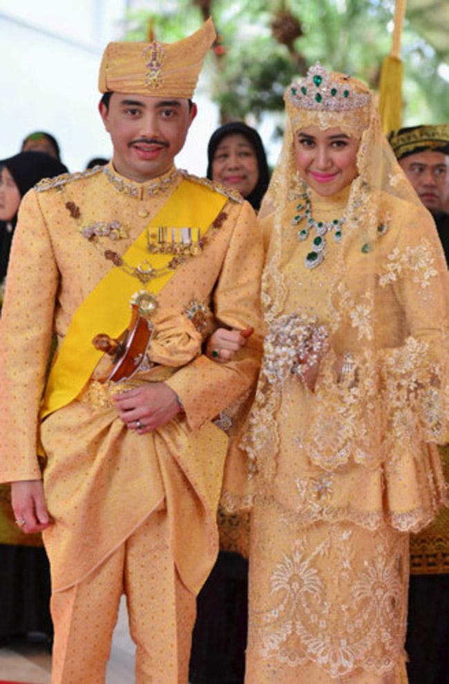 """Vợ Hoàng tử Brunei được thiết kế theo lối trang phục truyền thống. Bộ trang phục có mức giá khủng khiphần renmạ vàng, thân váy được đính viên kim cương và đá quý. Hai vợ chồng thể hiện """"quyền lực ngầm"""" thông qua trang đám cưới."""