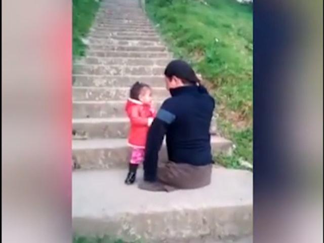Ông bố cụt chân bế con trên vai, dùng 1 tay leo từng bậc cầu thang