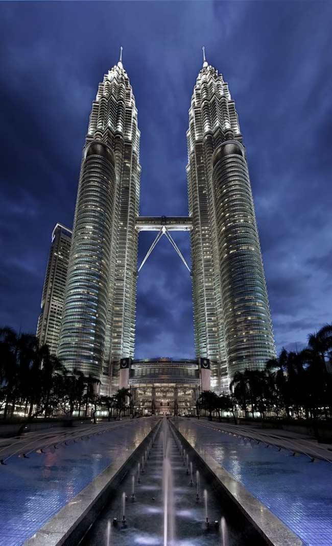 1. Tòa tháp đôi Petronas  Công trình kiến trúc nổi tiếng đầu tiên phải kể đến nằm ở Kuala Lumpur, Malaysia. Đó chính là tòa tháp Petronas hay còn có tên gọi khác là tháp đôi Petronas. Từ năm 1998 – 2008, Petronas là tòa tháp cao nhất trên thế giới. Chúng cũng là dấu ấn của thành phố Kuala Lumpur. Hai tòa tháp xinh đẹp này được thiết kế bởi kiến trúc sư người Argentina César Pelli và đi theo phong cách hậu hiện đại, đơn giản nhưng táo báo.