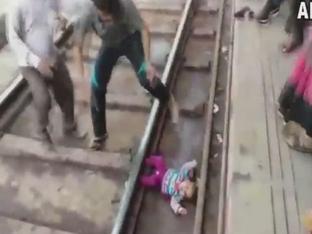Đứng tim cảnh em bé 1 tuổi nằm dưới gầm tàu hỏa đang chạy