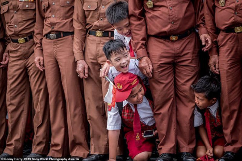 Các cậu bé học sinh Tiểu học tò mò chui qua hàng của cựu chiến binh tại một sự kiện ở Indonesia. Ảnh: Donny Herry